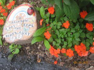 "Garden art featuring a stump, a rainbow, and the text ""A Rainbow Keeps the Blues Away"""