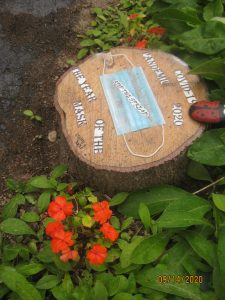A piece of garden art using a stump, flowers, and a medical mask