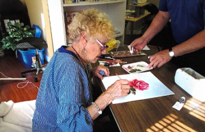 A woman working on a painting of a flower